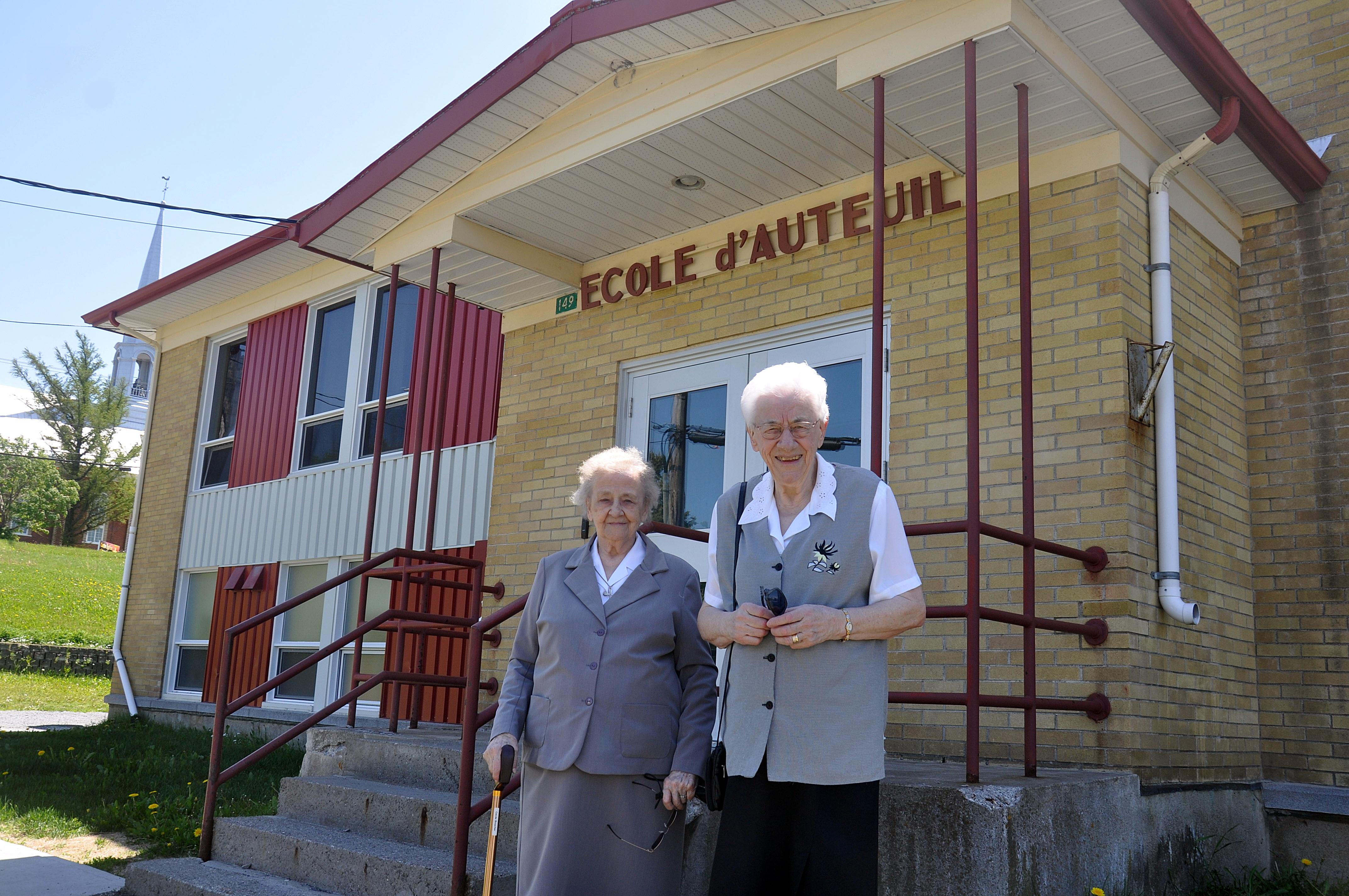 Cécile Boucher et Eva-May Michaud posent devant l'établissement où elles ont enseigné il y a 6 ans.