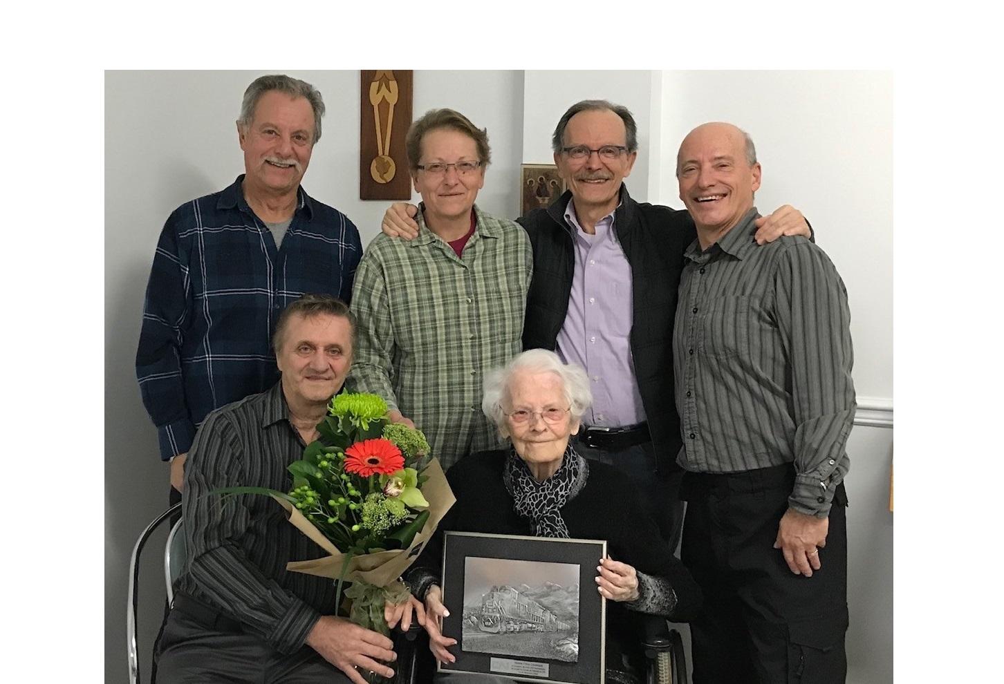 Hélène Fillion-Levesque est entourée de quatre de ses cinq enfants. À l'avant, William Théberge du CN et la centenaire. À l'arrière ses enfants : Réjean, Lynda, Christian et Benoit Levesque. Absent de la photo, Jacques.